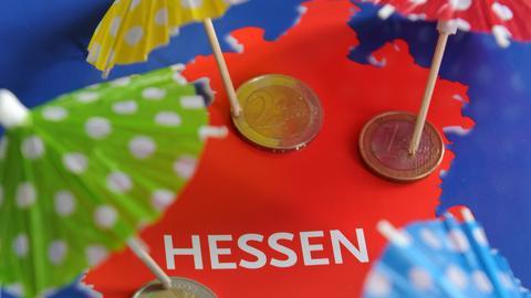 Symbolbild Schutzschirm Hessische Kommunen: Eisschirmchen und Eurostücke liegen auf hessischer Landkarte