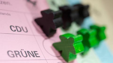 Schwarze und grüne Holzspielfiguren auf einem Wahlzettel