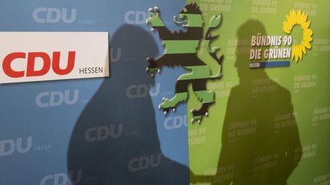 Schatten von Bouffier und Al-Wazir auf schwarz-grünen Plakaten zur Regierungsbildung 2013 in Hessen