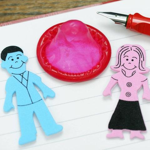 Figuren von Mann und Frau zwischen einem Kondom.