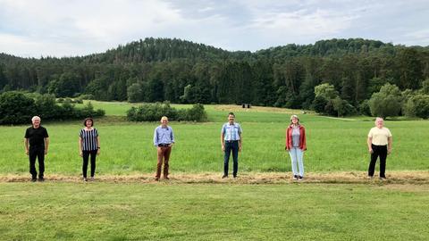 Fünf Menschen in einer Reihe auf einem Feld