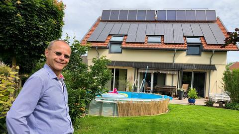 Mann steht vor einem Einfamilienhaus mit Solarkollektoren und Photovoltaikanlage