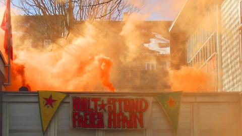 """Rauchtöpfe und Transparent mit der Aufschrift """"Halt Stand Freies Afrin""""."""