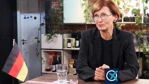 FDP-Spitzenkandidatin Bettina Stark-Watzinger im Vordergrund. Vor ihr steht eine kleines Fähnchen mit der Deutschlandflagge. Im Hintergrund eine Küchenzeile.