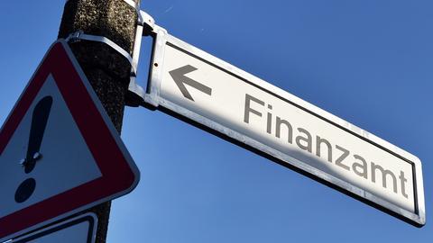 Ein Schild zeigt zum Finanzamt, davor ist ein Warnsignal zu sehen.