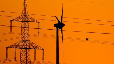Ein Windrad neben einem Strommast vor rotem Himmel.