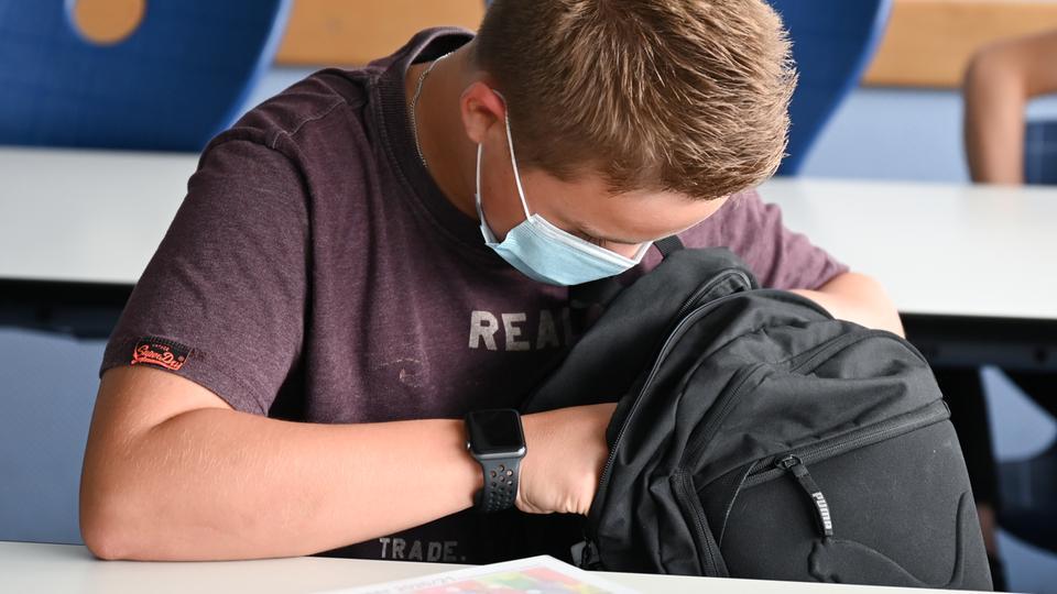 Ein Schüler mit Maske im Klassenzimmer