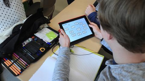 Ein Schüler blickt auf ein Tablet