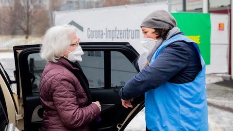 Eine per Taxi zum Impfzentrum beförderte Seniorin wird von einer Helferin in Empfang genommen.