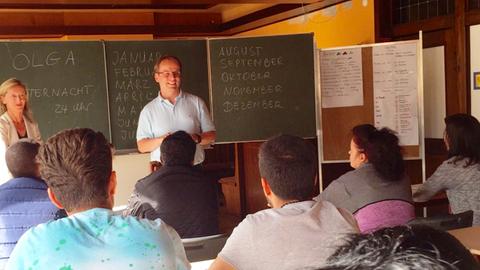 Timon Gremmels vor einer Klasse Flüchtlinge