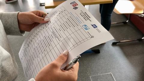 Hände einer Schülerin, die einen Wahlzettel hält