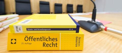 Das Foto zeigt zwei Bücher zum Thema Verwaltungsrecht, welche auf einem Schreibtisch in einem Gericht liegen.