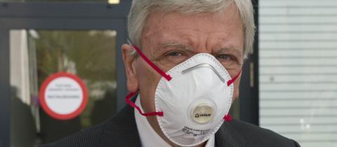 Der hessische Ministerpräsident Volker Bouffier mit einer Atemschutzmaske