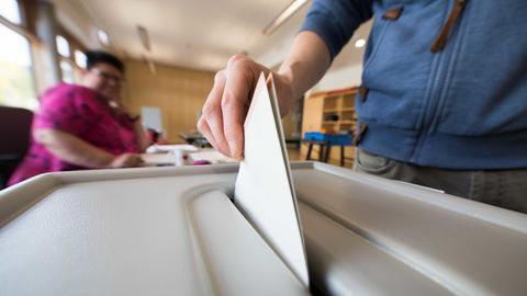 Mann wirft Stimmzettel in Wahlurne ein