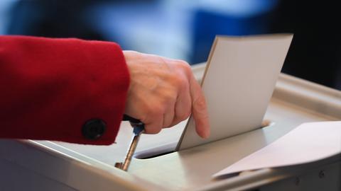 Eine Frau steckt einen Stimmzettel in eine Wahlurne.