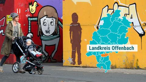 Frau mit Kinderwagen geht an Hauswand mit Graffitis vorbei