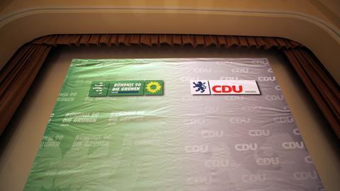 Eine Wand mit den Parteilogos von Grünen und CDU.