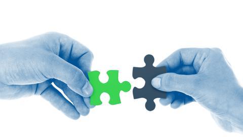 Hände halten schwarzes und grünes Puzzleteil nebeneinander
