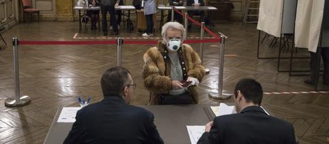 Wählerin in Frankreich mit Mundschutz