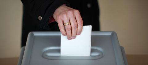 Wähler steckt Stimmzettel in Urne