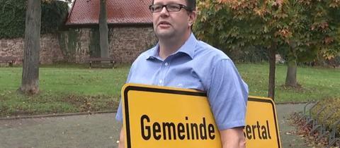 Wesertals Bürgermeister Cornelius Turrey mit einem Ortsschild unterm Arm