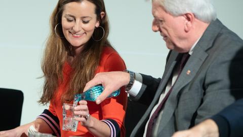 Ministerpräsident Volker Bouffier schenkt Linken-Politikerin Janine Wissler Wasser in ein Trinkglas ein