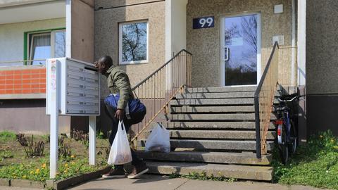 Ein Mann schaut in einem Briefkasten nach der Post.