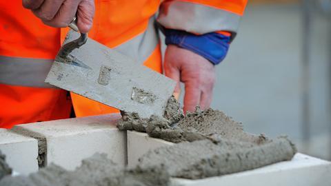 Ein Maurer verteilt mit einer Kelle Mörtel auf Verbundsteinen
