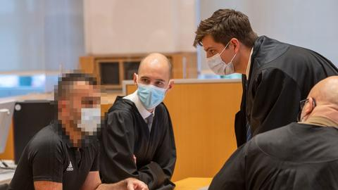 Der Angeklagte sitzt im Gerichtssaal und berät sich mit seinen Anwälten.
