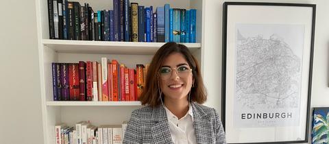 Reyhan Karadeniz steht vor einem Bücherregal