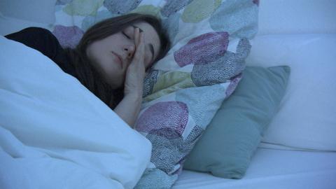 Eine Frau liegt im Bett und reibt sich die Augen.