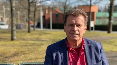 Ein Mann mit grauen Haaren sitzt in der Sonne auf einer Bank und lächelt in die Kamera. Er trägt ein rotes Hemd und ein blaues Jackett.