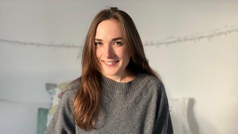 Eine Frau mit dunklen Haaren lächelt in die Kamera. Sie sitzt auf einem Bett und trägt einen grauen Pulli.