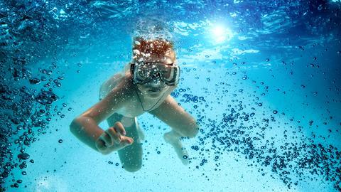 Ein Junge mit großer Tauchermaske im aufgewirbelten Wasser