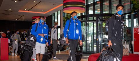 Hygiene muss sein: Die Skyliners erreichen in Masken ihr Teamhotel in München.