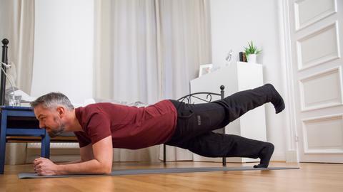 Ein Mann macht Fitness-Übungen zuhause