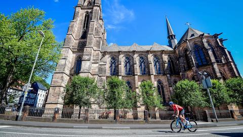 Radrennfahrer fährt an Marburger Elisabeth-Kirche vorbei