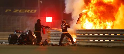 Stewards löschen das in zwei Teile gebrochene Wrack, aus dem Romain Grosjean wie durch ein Wunder aussteigen konnte.