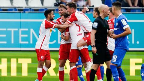 Regensburg bejubelt das 2:0. Ein Darmstädter lässt den Kopf hängen.