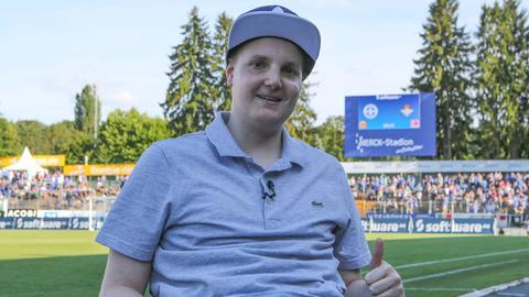Jonathan Heimes sitzt im Stadion in Darmstadt.