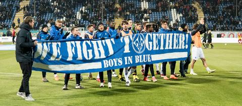"Lilien-Profis zeigen Fans das Banner ""We Fight Together"""