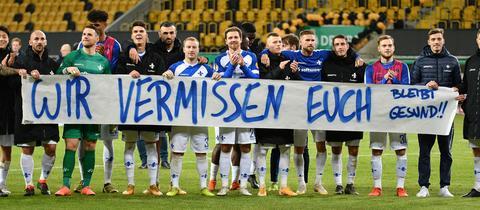 """Spieler von Darmstadt 98 mit einem Banner """"Wir vermissen Euch"""""""