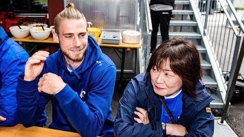Lilien-Profi Felix Platte sitzt am Tisch mit Fan Kyoko aus Tokio