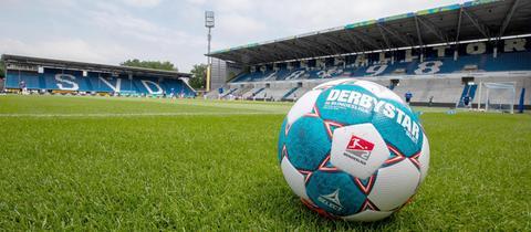 """Ein Fußball liegt im Vordergrund des Bildes auf dem grünen Rasen des Stadions von Darmstadt 98. Im Hintergund leere Tribünen auf denen """"SVD"""" zu lesen ist."""