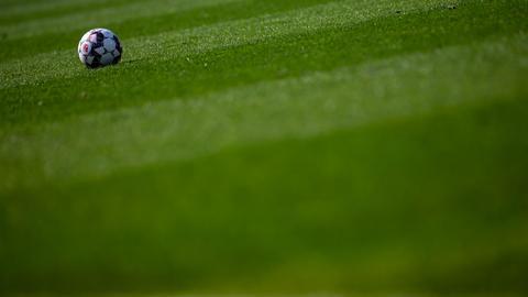 Ein Fußball liegt auf einem Fußballplatz.