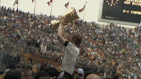 Eintracht-Spieler Grabowski hält den Pokal hoch.