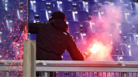 Ein vermummter Frankfurter Anhänger schleudert einen brennenden Bengalo von der Tribüne. Die Partie dürfte für Frankfurt ein Nachspiel haben.