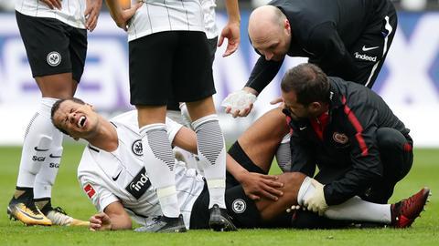 Chandler mit schmerzverzerrtem Gesicht am Boden, wird behandelt.