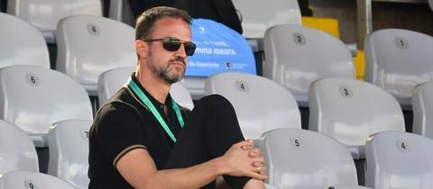 Fredi Bobic sitzt mit Sonnenbrille auf der Tribüne im Grünwalder Stadion in München