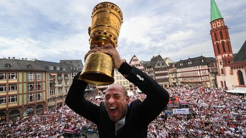 Eintracht-Präsident Peter Fischer jubelt mit dem DFB-Pokal auf dem Römer-Balkon